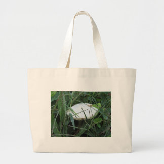 White mushroom on a green meadow large tote bag