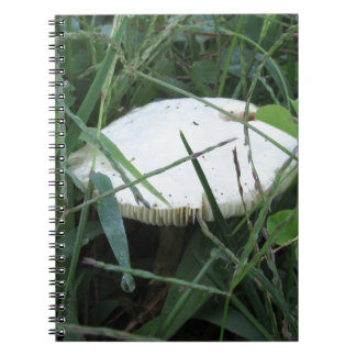 White mushroom on a green meadow spiral notebook