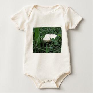 White mushroom on a green meadow baby bodysuits