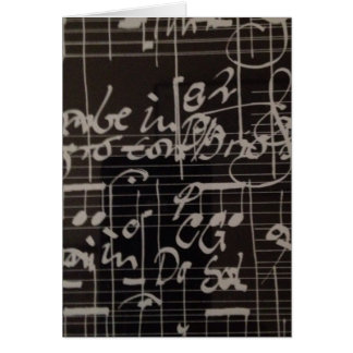 white music notation on black background card
