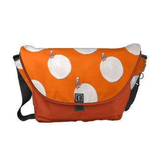 White ornamental pumpkins on orange messenger bags