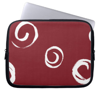 White paint swirls on red laptop sleeve