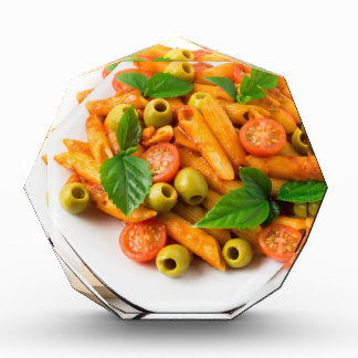 White plate of penne pasta decorated with cherry acrylic award