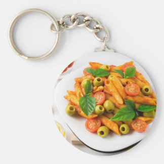 White plate of penne pasta decorated with cherry keychain