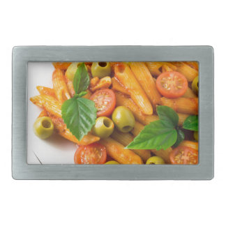 White plate of penne pasta decorated with cherry rectangular belt buckle