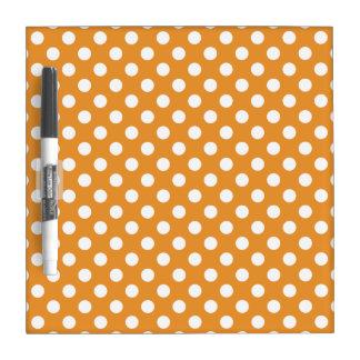 White polka dots on amber dry erase board