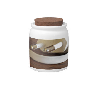 White smartphone charger on wooden table candy jar