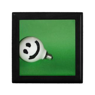 White smiling bulb on green background gift box