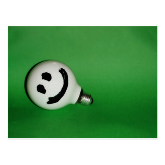 White smiling bulb on green background post card