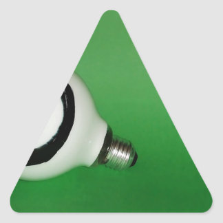 White smiling bulb on green background triangle sticker