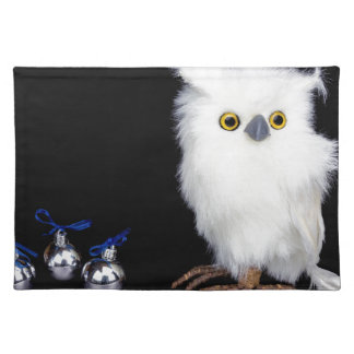 White snowy owl figurine with silver christmas cloth placemat