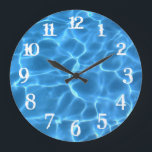 """White Splash Numbers Blue Swimming Pool Large Clock<br><div class=""""desc"""">Add your own photo or personalized text to create your own wall clock. You can change the color of the wall clock numbers from white to something that matches your photo if needed. Photo of light playing on the bottom of a swimming pool digitally tinted bright blue.</div>"""
