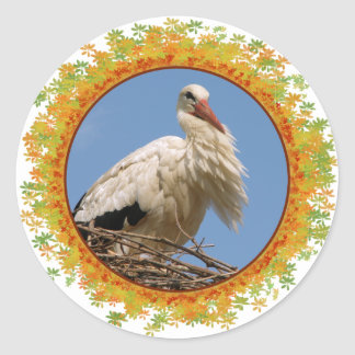 White stork in its nest in frame of leaves classic round sticker