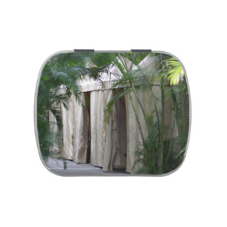 white tents behind palm fronds safari jelly belly candy tin