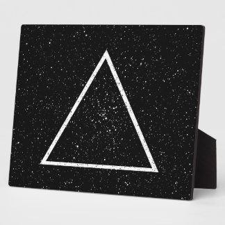 White triangle outline on black star background plaque