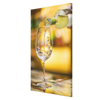 White wine is poured from bottle in restaurant. canvas print