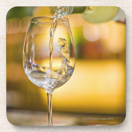 White wine is poured from bottle in restaurant. coaster