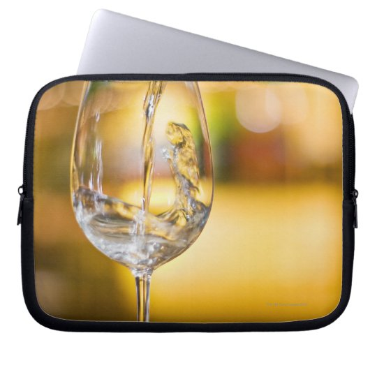 White wine is poured from bottle in restaurant. computer sleeve