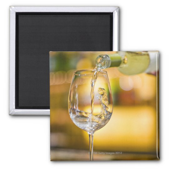 White wine is poured from bottle in restaurant. magnet