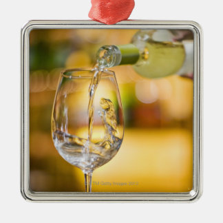 White wine is poured from bottle in restaurant. metal ornament