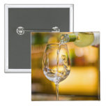 White wine is poured from bottle in restaurant. pinback button