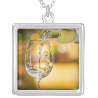 White wine is poured from bottle in restaurant. silver plated necklace