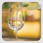 White wine is poured from bottle in restaurant. square sticker