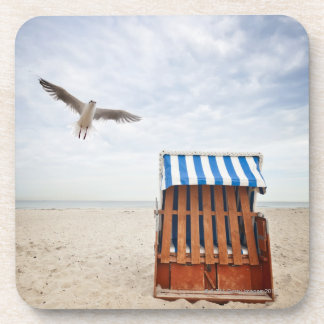 Wicker beach chair on beach drink coaster