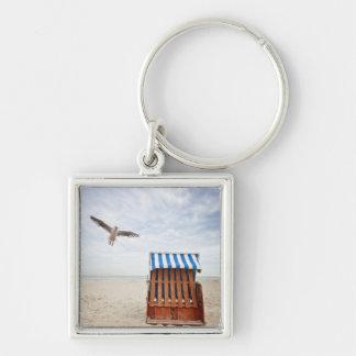 Wicker beach chair on beach keychain
