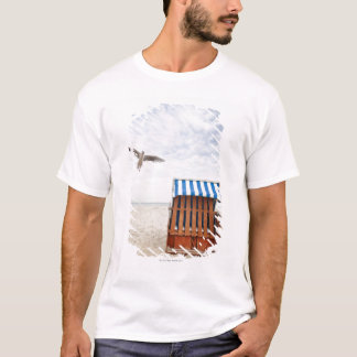 Wicker beach chair on beach T-Shirt