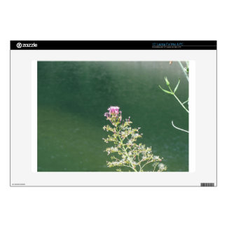 Wildflowers against the water surface of a river laptop decal
