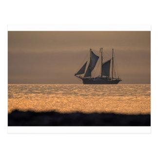 Windjammer en luz de la puesta del sol postales