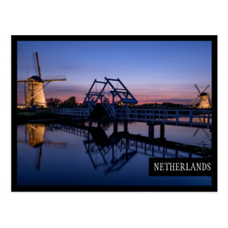 Windmills and a drawbridge at sunset edge postcard