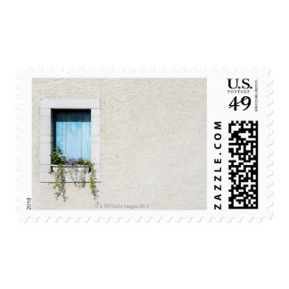 Window and window-box of flowers in plain wall postage