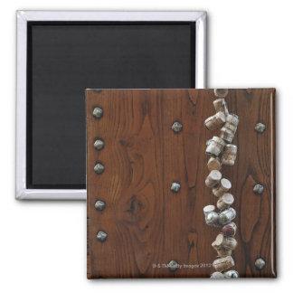 Wine corks hanging on wooden door refrigerator magnets