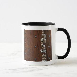 Wine corks hanging on wooden door mug