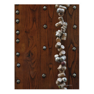 Wine corks hanging on wooden door postcard