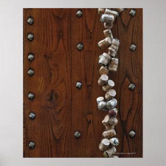 Wine corks hanging on wooden door poster