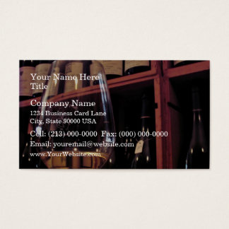Wine glass with bottles in background business card