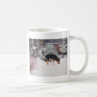 Winter snow scene with cute black and tan dog coffee mug
