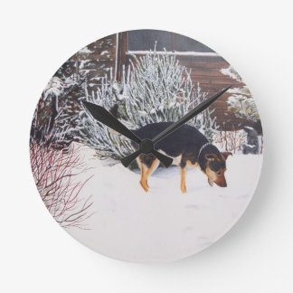 Winter snow scene with cute black and tan dog round clock