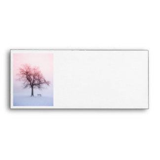 Winter tree in fog at sunrise envelope