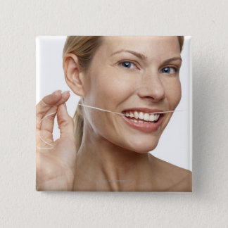 Woman against white background flossing teeth, button