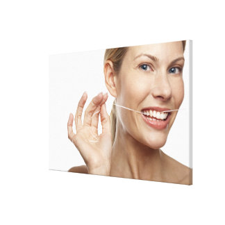Woman against white background flossing teeth, canvas print
