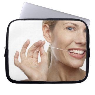 Woman against white background flossing teeth, laptop sleeves