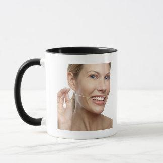 Woman against white background flossing teeth, mug