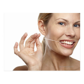Woman against white background flossing teeth, post card
