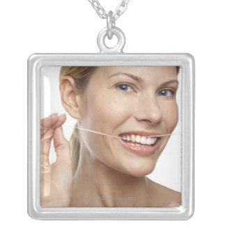 Woman against white background flossing teeth, silver plated necklace