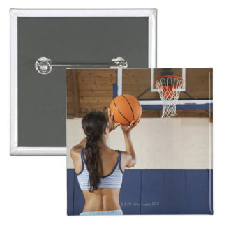 Woman aiming at hoop with basketball, rear view 2 inch square button