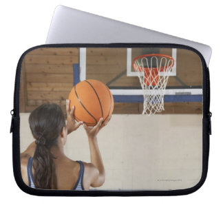 Woman aiming at hoop with basketball, rear view computer sleeve